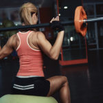 Young sporty woman lifting barbell sitting on fitball in fit class. Slim female with muscular body exercising in the gym.